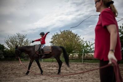 """""""Nagyon szerencsés, aki a lovakkal megtalálja azt a biztos pontot, azt a kapaszkodót, ahova mindig vissza lehet térni. Persze bármi más lehet ilyen horgony, ami belülről építi az embert, lehet a zene, vagy lehet a mozgás, vagy lehet a sport, de ezeknél, úgy érzem, az ember inkább befogadó, és ritkábban ad. A lóval való munka azért nagyon fontos, mert ott mindig kétirányú ez a dolog"""" - mondja Kata. Barnus kisebb mozgászavarral érkezett az alapítványhoz, de aki lovagolni látja, érzi, hogy ő már megtalálta ezt a bizonyos """"biztos pontot""""."""