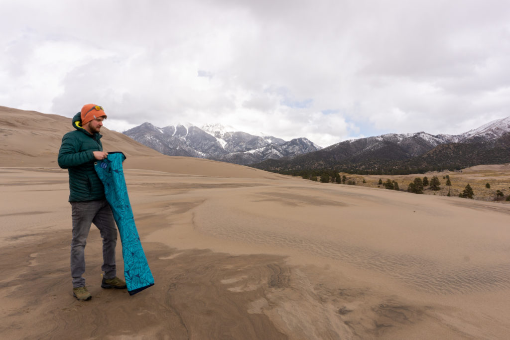 rugged tarpestry laying out sand dunes