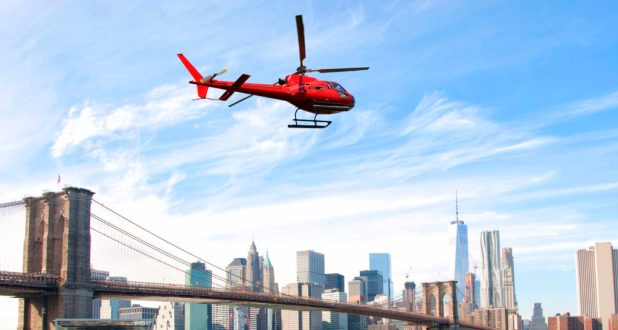Uber Helicopter flying over New York City skyscrapers and Brooklyn Bridge, USA