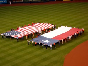 Large American Flags have long beena tradition at sporting events. This past weekend stadiums across the country honored Veterans and America with flags and tributes. One tribute let a sour taste however. Photo R. Anderson