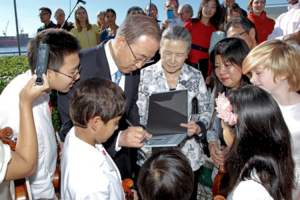 Pictured is UN Secretary-General Ban Ki-moon (centre), accompanied by his wife, Yoo Soon-taek (centre) signing an autograph for the young Tarumi Violinists who performed at the annual International Peace Bell ceremony (September 21). UN Photo/Paulo Figueiras)