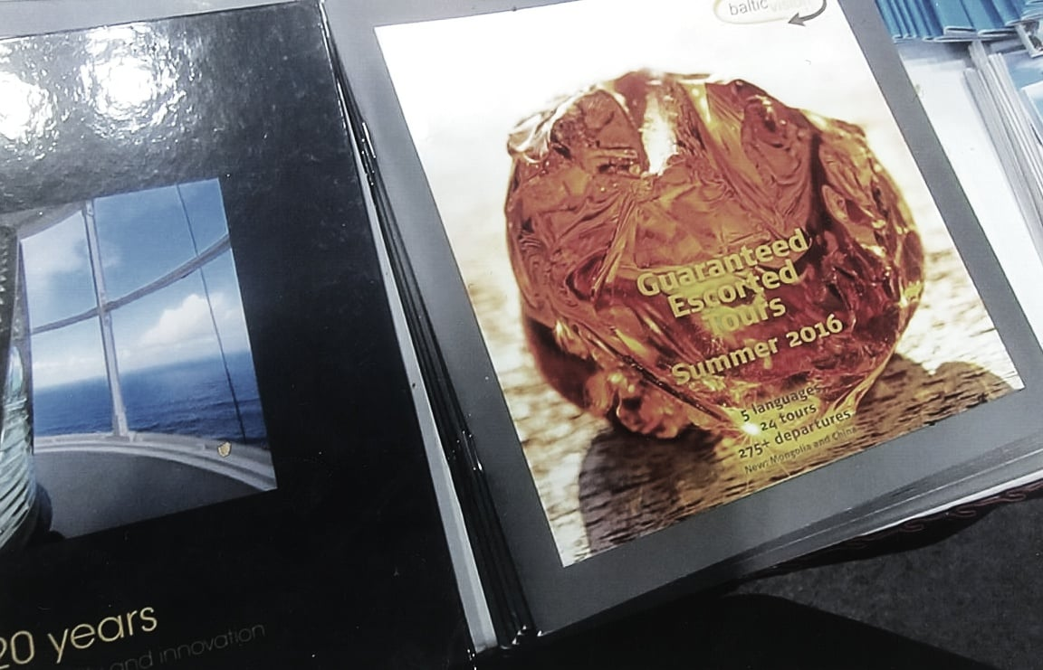 "Shown here next to the book entitled ""VIA HANSA – 20 years – Service, sustainability, and innovation"" is a Baltic vision brochure on ""Guaranteed Escorted Tours Summer 2016."" Photo: Ann Charles"