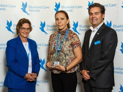 Egidija (centre) being presented with her award by Bridget Warr CBE, Chief Executive of the United Kingdom Homecare Association and Duncan Berry, Chief Operating Officer of Bluebird Care