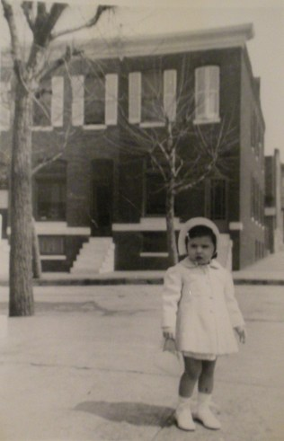 Young Barbara Duffy posing in front of row homes on the 600 block of South Streeper Street, the next street over from Kenwood Avenue c. 1942