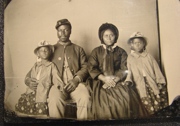 A black man in uniform and a black woman wearing a dress and bonnet sitting for a portrait with their two daughters on each side.