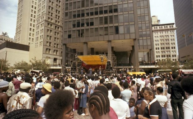 A crowd of African American people looking towards a stage set up in front of a large modern office building.