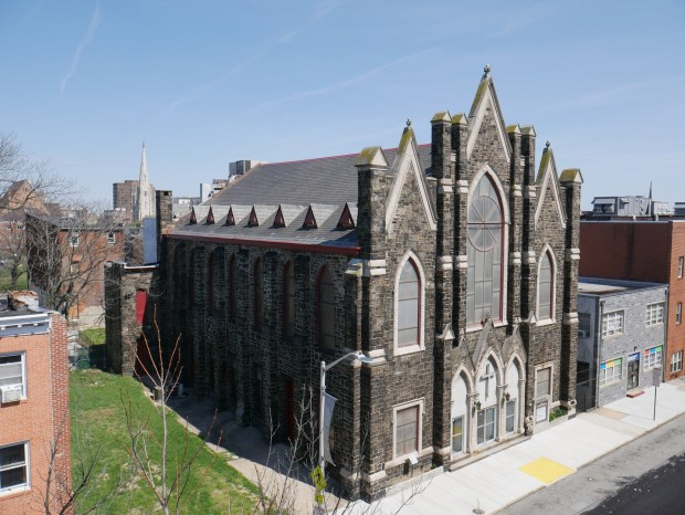 A gothic stone church seen from the roof of a building across the street.