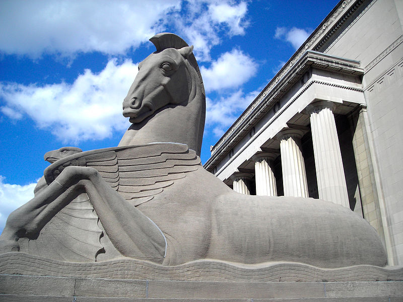 A stone sculpture of a horse sitting on an abstract wave with columns in the background.