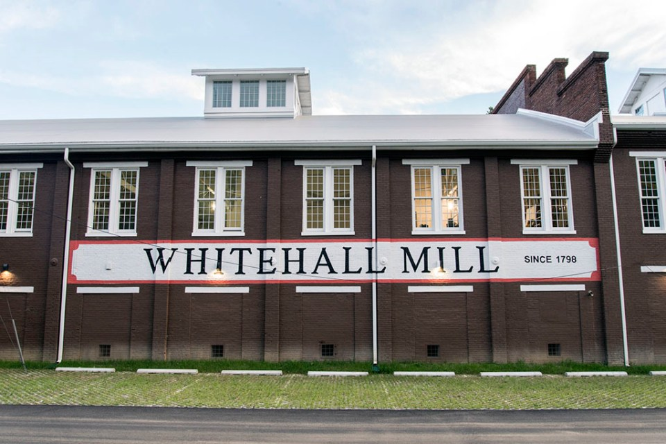"""Large brick building with a sign reading """"Whitehall Mill"""" painted on the side."""