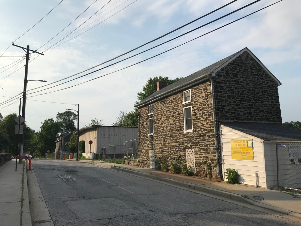 A stone house with a smaller white addition on a narrow road. A large yellow sign is attached to the white addition as a demolition notice.