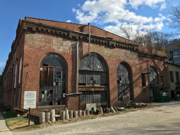 A large brick industrial building with three tall arched opening filled with a grid of small window panes.