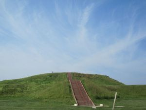 Steps running up a large earthern mound covered in green turf.