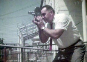 A man in a white shirt holding a small film camera to his eye while standing in front of a building.