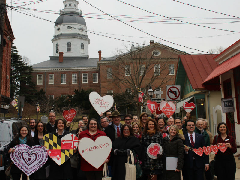 Group of people holding paper hearts to show support for preservation at the Maryland State House.