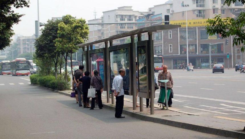 Sommer in Chengdu: Menschen warten im schmalen Schatten einer Bushaltestelle