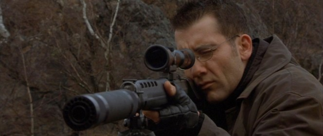 Although the gunshots sound suppressed in the film, the attachment to his barrel would actually be very useless here.