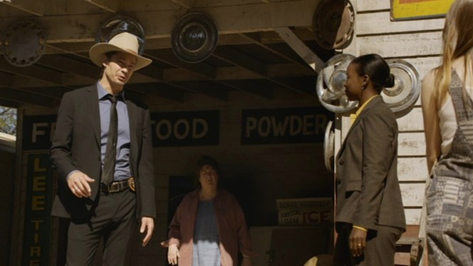 """Raylan sports a black suit, solid blue shirt, and black subtly-patterned tie for his investigation in Harlan County in """"The Moonshine War"""" (Episode 2.01)."""