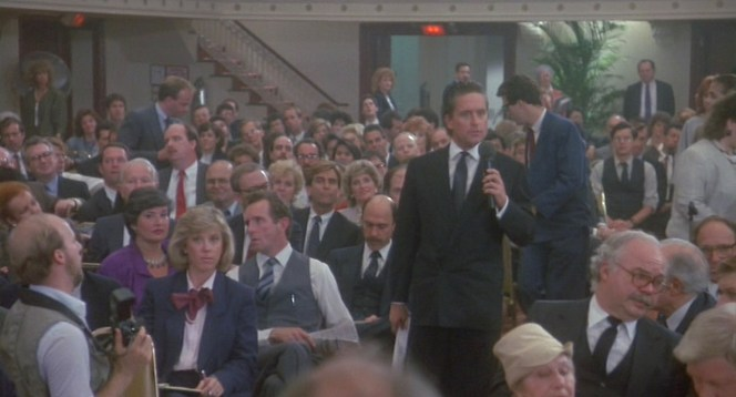Gekko controls the room during the Teldar Papers shareholder meeting.