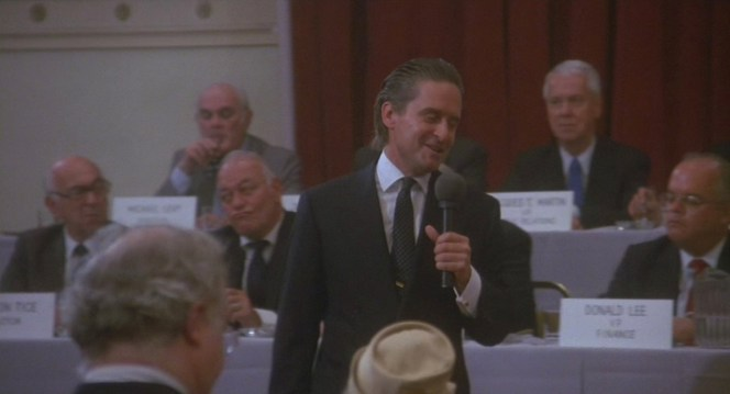 Gordon Gekko breaks workplace decorum by actually cracking a smile during a meeting.