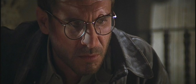 To the best of my recollection, Indy only wears his glasses with his adventurer outfit in Raiders of the Lost Ark. Otherwise, they are relegated only to be worn with his professorial suits.