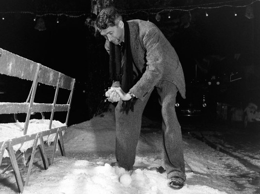 """Jimmy Stewart playing with the """"chemical snow"""" behind-the-scenes of It's a Wonderful Life, captured by Life photographer Martha Holmes who visited the Encino set in the summer 1946."""
