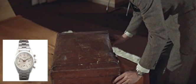 Bond flashes his Rolex while opening one of his battered brown leather suitcases.