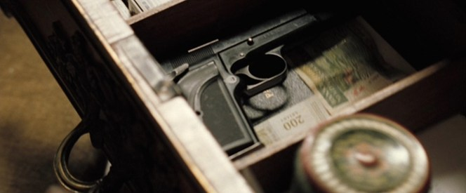 The Nambutu ambassador's Browning Hi-Power Mark III sits in his desk.