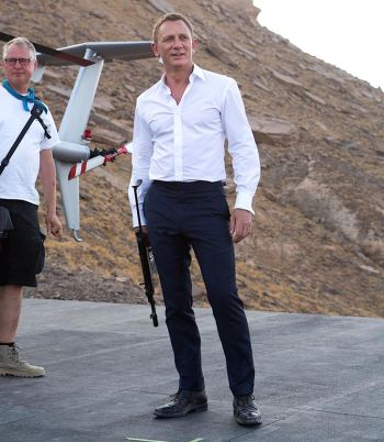 Craig on set, with small trousers and a large weapon.