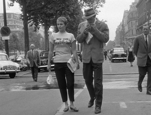 """The two pallid-looking businessmen on either side of our protagonist couple are dressed similarly to Michel in light jackets, dark trousers, and ties, but Belmondo's character is clearly not one of them. Nevertheless, the """"uniform"""" shows his effort to blend in to the world of 1959 Paris... hampered by his own instincts to stand out with swagger."""