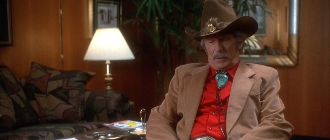 """Surprisingly, Webb wears a cowboy hat while indoors in each of his appearances – an oddity for a man who uses phrases like """"little lady""""– and who would normally remove his hat upon entering a building."""
