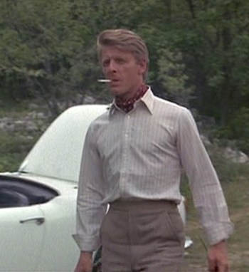 Edward Fox in The Day of the Jackal, carrying a custom rifle in front of his 1961 Alfa Romeo.