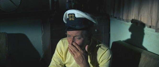 Pretty wiped after a long day, Tony Rome still keeps his wits about him enough to needle a couple of meatheaded henchmen who snuck onto his boat.