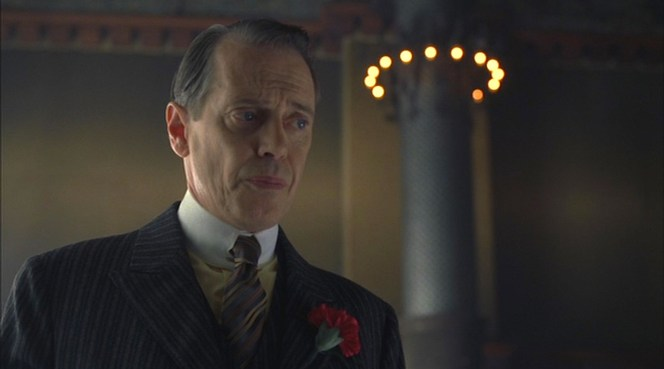 """The Ivory Tower"" (episode 1.02): Nucky grimaces during a meeting with the Commodore, wearing a solid yellow shirt with a multi-striped tie."