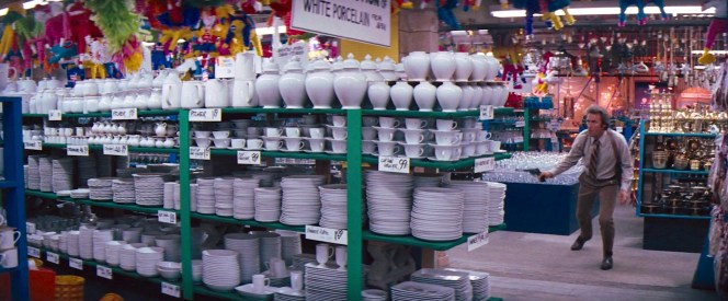 Harry darts through the aisles of hte grocery store in search of his target. Those shelves of white porcelain vases and flatware surprisingly made it through this action scene mostly intact!