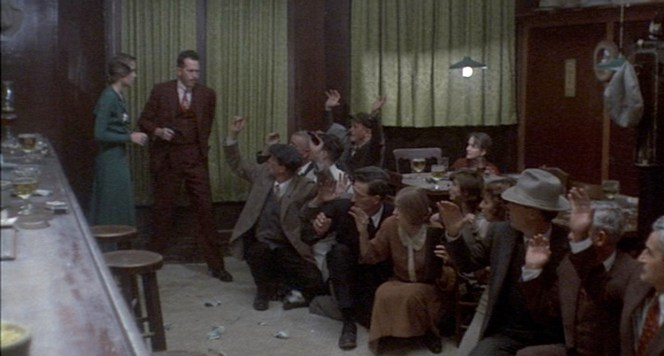 Believing himself to have proven his bravado to Billie, Dillinger takes the money he just robbed from the barroom denizens and scatters it onto the ground.