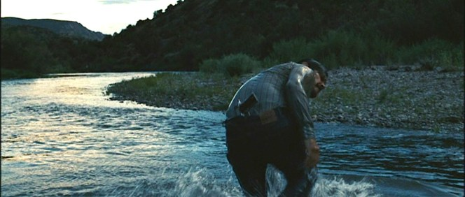 The distinctive Levi's patch of Llewelyn's jeans is seen as he makes it to shore with his 1911A1 stuck in his waistband.
