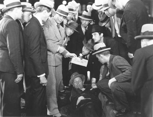 Promotional image of Tony and his crew discovering the corpse of a fellow gang member. Tony's spats protect those patent leather shoes of his against the dirty street.