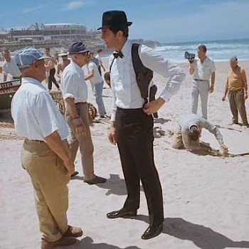 Lazenby on location in Portugal, still wearing Bond's trilby, bow tie, and shoulder holster.