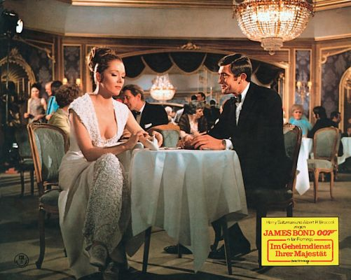 This German lobby card for Im Geheimdienst Ihrer Majestät features a full shot of Tracy and Bond in the dining room of the Hotel Palácio.