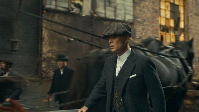 Tommy Shelby's standard look for the first season: dark gray three-piece suit, stiff white club collar with no tie, tweed newsboy cap with a stitched-in razor blade, and gold pocket watch chain... all worn with a cynical yet confident stride.