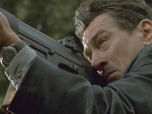 Sam takes aim with his SIG SG 551 rifle, offering audiences a fine glimpse of his vintage Jardur chronograph wristwatch.