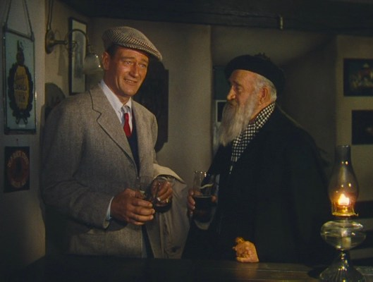 The bearded fellow joining John Wayne for a swig of porter is Francis Ford, brother of director John Ford who would appear in many of his films.
