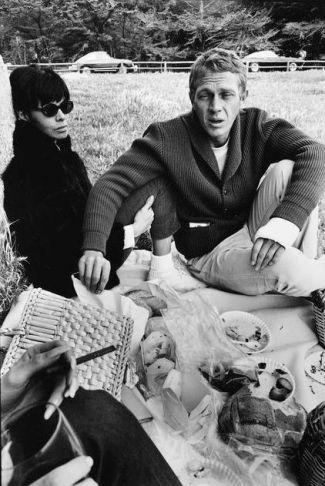 Neile and Steve share a picnic with Peggy and Clax. Note the cast on Steve's wrist and his Ferrari parked in front of Clax's Porsche behind them. (Photograph by William Claxton, 1964)