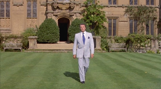Marlowe crosses the lawn in his light summer suit and contrasting black loafers.