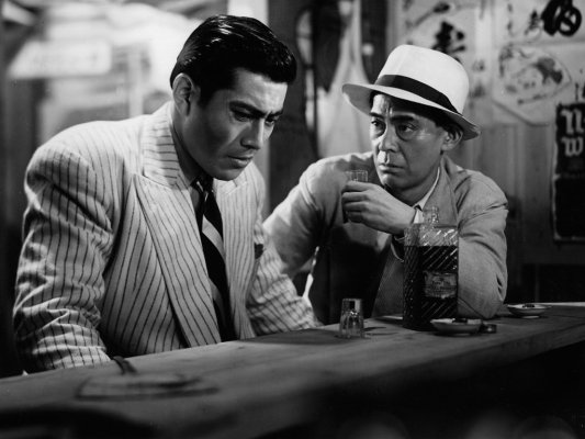 Production still of Reisaburo Yamamoto as Okada, offering a shot of Nikka Whisky (advertisement also seen over Yamamoto's left shoulder) to Matsunaga (Toshiro Mifune).