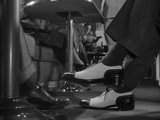 The contrast of Bruno's bolder suit trousers and two-tone shoes communicate that he will be the agent of chaos for the more soberly dressed gentleman with whom he collides on the train.