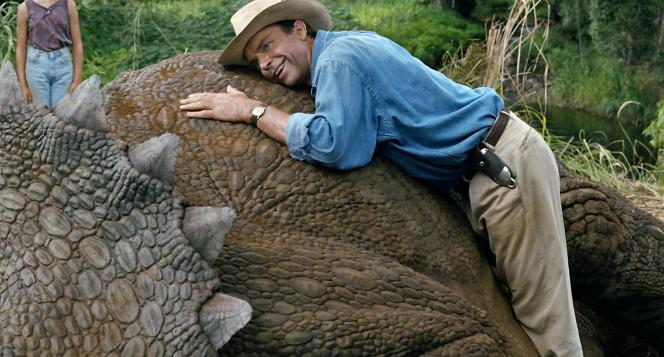 Production photo of Sam Neill with Dr. Alan Grant's silver U-Dig trowel visible on the left side of his belt as he makes the acquaintance of a sickly Triceratops.