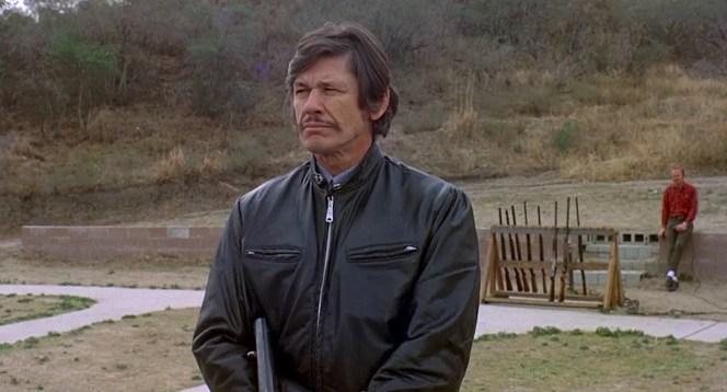 A stoic Arthur Bishop observes Steve's shooting technique.