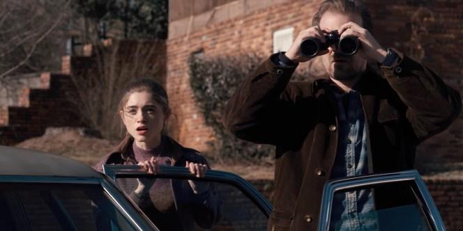 Nancy Wheeler (Natalia Dyer) stands with Hopper as he watches Martin Brenner's henchmen search the Wheeler home.