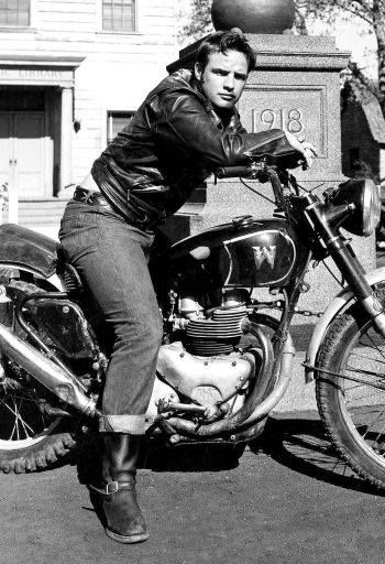 "Costumed in his moto jacket, jeans, and engineer boots, Marlon Brando poses on a Matchless motorcycle used by stunt rider Wally Albright; note the inverted ""M"" to resemble a ""W""."